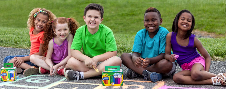 Young children sitting on sidewalk with Crayola chalk